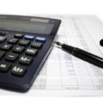 Calculator and pen on balance sheet